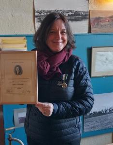 Karin Härjegård med medaljen föst på sin blå täckjacka håller upp sitt diplom.