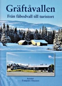 En fäbodvall på vintern med fjäll bakom och en turistanläggning.